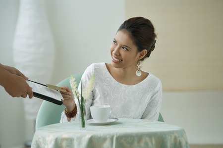 Young woman sitting in restaurant, being handed a menu Imagens