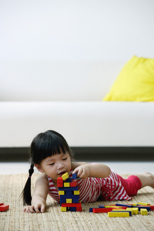 A small girl plays with blocks on the floor LANG_EVOIMAGES