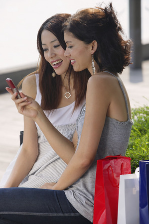 Women sitting on bench, looking at mobile phone