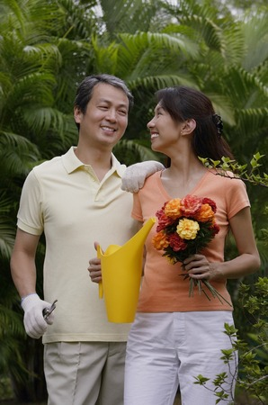 homeownership: Couple in garden, woman holding bouquet of flowers and watering can, smiling at man next to her