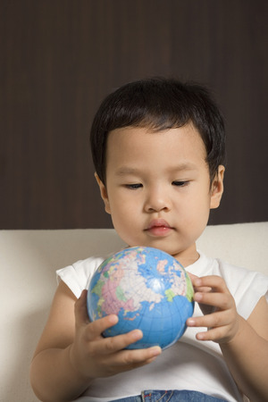 world at your fingertips: Baby boy looking at globe