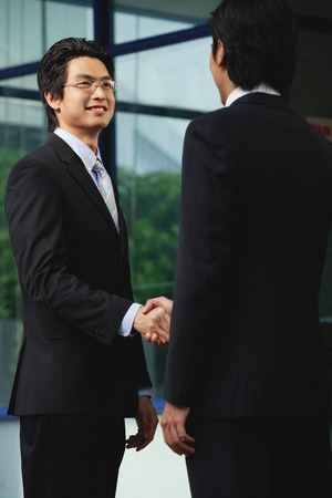Two men wearing suits shake hands 스톡 콘텐츠