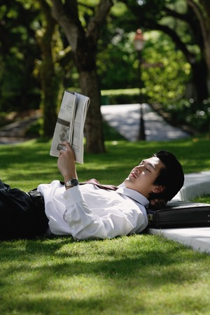 professionally: A man lies down and reads the newspaper in the park