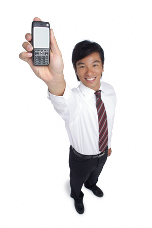 professionally: A man smiles at the camera as he holds out his cellphone LANG_EVOIMAGES