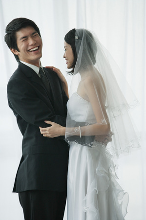 wholeness: A newlywed couple stand with their arms around each other LANG_EVOIMAGES