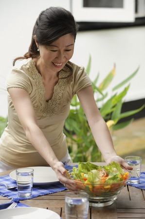 homeownership: Woman setting a table for a meal, putting bowl of salad on the table