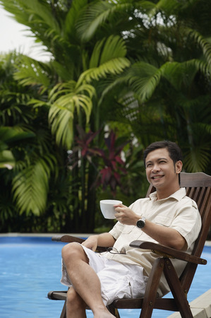 Man sitting by swimming pool, holding a cup of coffee, smiling