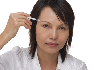 only 1 person: Woman applying make-up while looking at camera