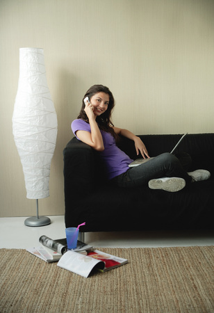 A teenage girl sits on the couch and talks on the phone Archivio Fotografico