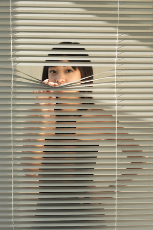 Young woman behind Venetian blinds