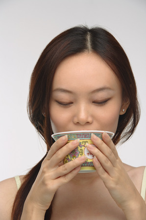 only 1 person: Young woman drinking tea from traditional tea cup LANG_EVOIMAGES