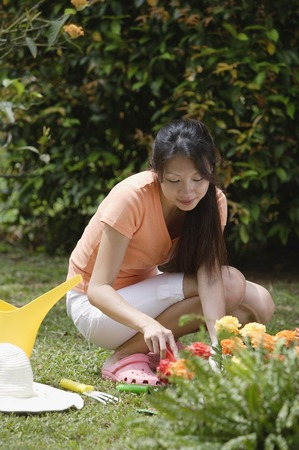 homeownership: Woman gardening outdoors LANG_EVOIMAGES