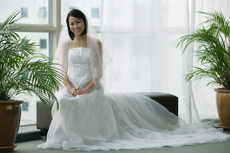 fulfil: A bride with a white wedding gown sits down and smiles at the camera