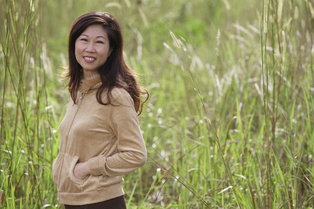 one mature woman only: woman standing in tall grass, nature, smiling at camera