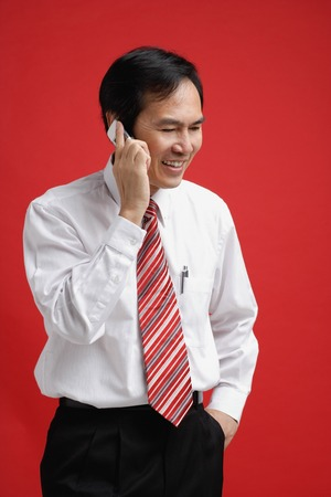 A man smiles as he talks on a cellphone