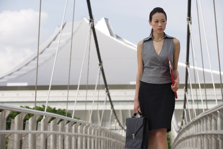 Businesswoman walking while looking into distance