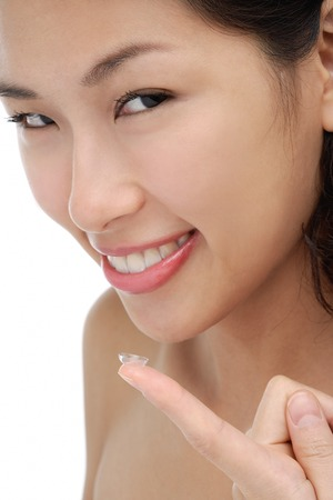 A young woman smiles at the camera a she puts a contact lens in