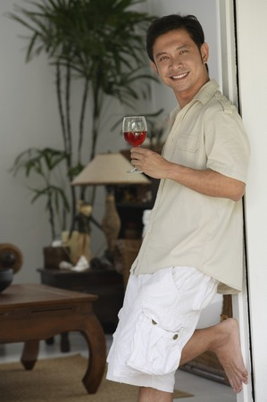 homeownership: Man leaning against doorway, holding glass of wine LANG_EVOIMAGES