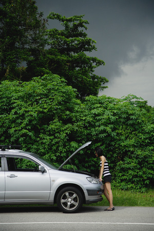 A woman checks under the hood of her car