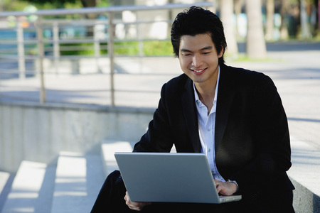 professionally: A man uses his laptop outdoors