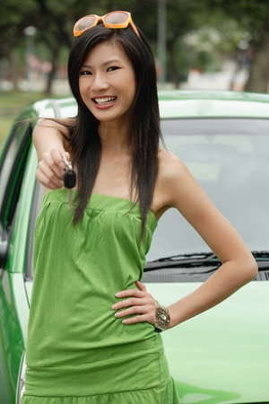 oriental ethnicity: A young woman in a green dress with a green car LANG_EVOIMAGES