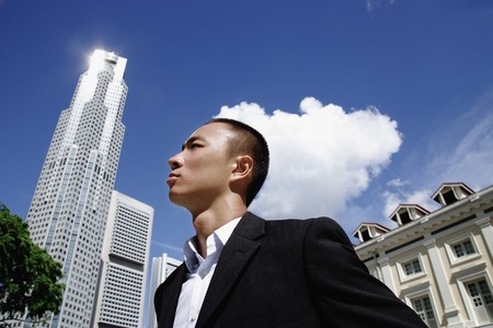 professionally: A man in a suit with a skyscraper behind him LANG_EVOIMAGES