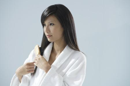woman bathrobe: woman wearing bathrobe, brushing hair and looking away from camera LANG_EVOIMAGES