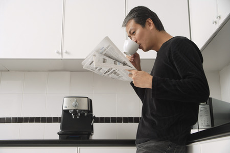 affluence: Man in kitchen, drinking coffee and reading paper