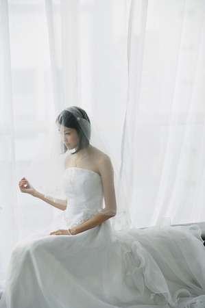 commit: A bride with a white wedding gown sits down LANG_EVOIMAGES
