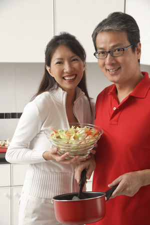 Man and woman in kitchen cooking, holding salad, looking at camera, smiling