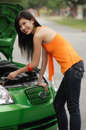 A young woman looks under the hood of a car