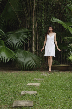 stepping: Woman in garden, walking on stepping stones LANG_EVOIMAGES