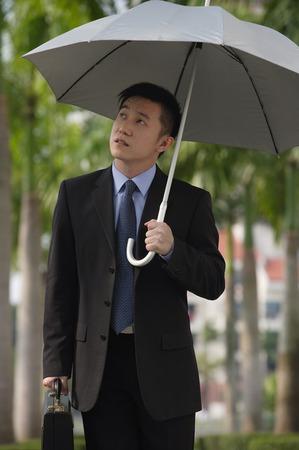 only 1 person: Businessman holding umbrella LANG_EVOIMAGES