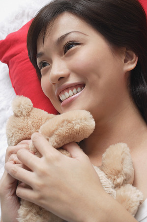 only 1 person: Young woman playing with teddy