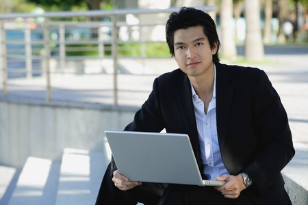 professionally: A man uses his laptop outdoors while he looks at the camera LANG_EVOIMAGES