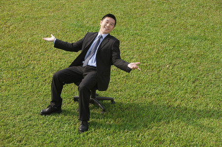 laid back: Businessman sitting on an office chair, smiling at camera