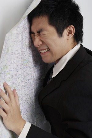 frustrated man leaning against map