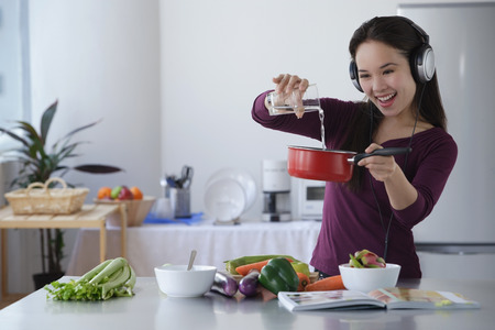 Young woman cooking while listening to music