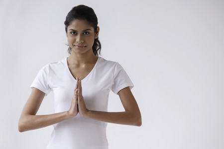 Woman standing with hands in namaste, prayer, looking at camera