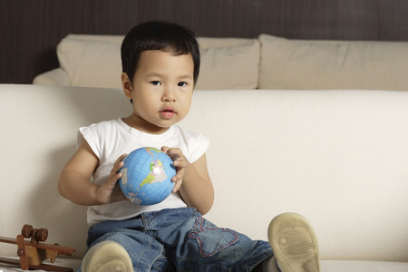 world at your fingertips: Baby boy holding globe looking at camera