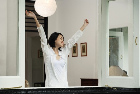 only 1 person: A woman stretches out her arms in her house