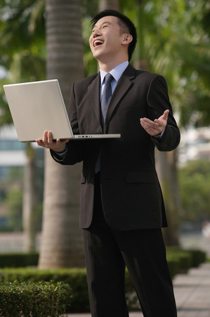 Businessman holding laptop and laughing