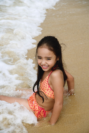 Young girl sitting on beach with waves crashing over her, smiling