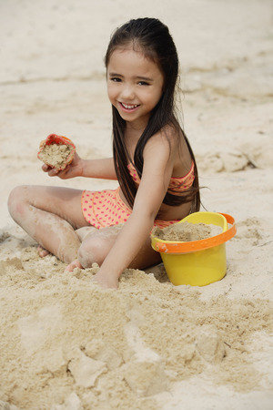 sand castle: Young girl building sand castle on beach, smiling LANG_EVOIMAGES