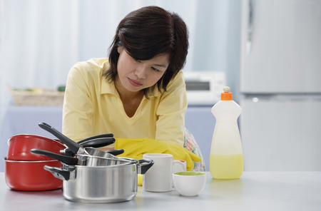 Woman in kitchen, leaning on kitchen counter, looking at stack of pots and pans