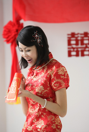 wedding customs: A bride looks excited as she looks inside a red envelope