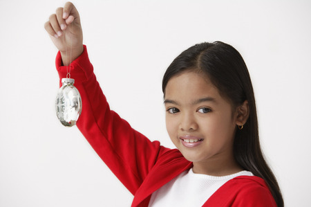Girl holding up Christmas ornament looking at camera Stock Photo