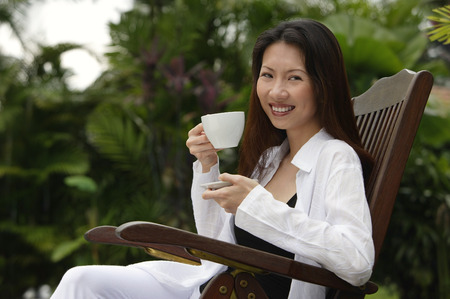 resort life: Woman sitting outdoors, having a cup of tea, smiling at camera