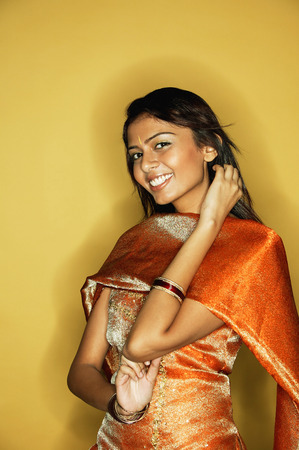 Woman in Indian clothing, smiling at camera, hand on neck LANG_EVOIMAGES