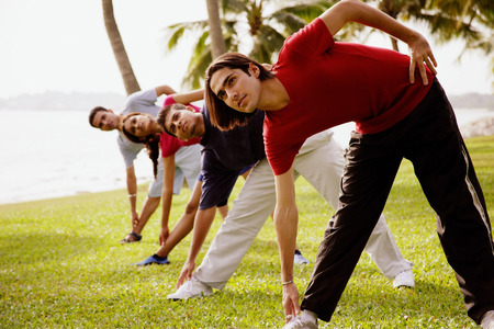 adults: Young adults doing stretching exercises